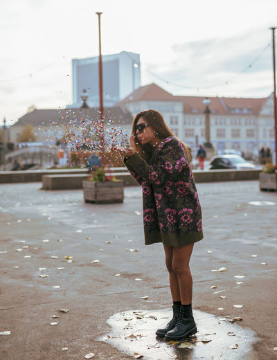 Woman Blowing Confetti While Standing In City