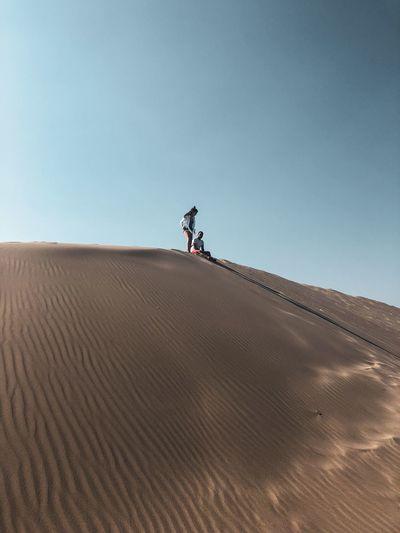 Couple on sand at desert against sky