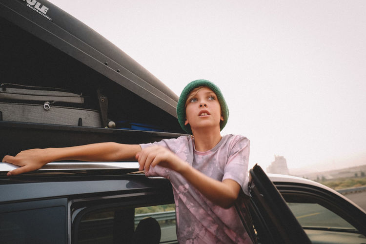 Portrait of young woman standing by car against sky