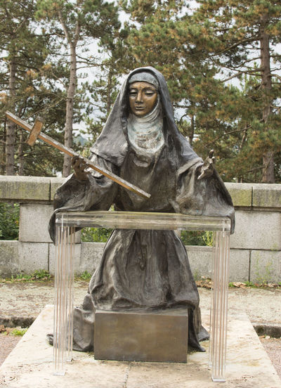 Statue of St Therese Basilica Lisieux Lisieux Basilica St Therese Statue Tree Day Kneeling No People Nun Nuns Habit Outdoors Praying Religion Religious Statues Sculpture Statue Stone Wall Sword Tree