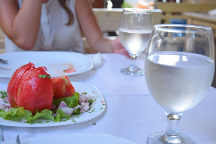 Midsection Of Woman Having Food At Table In Restaurant