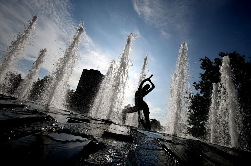 Man splashing water against sky