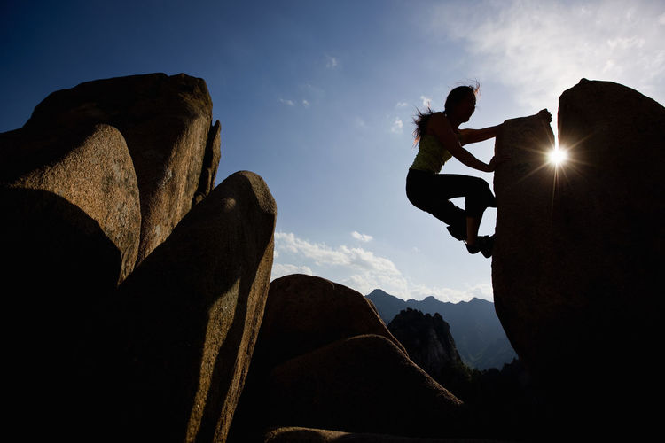 Low angle view of silhouette person on rock against sky