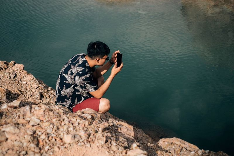 High angle view of young man photographing with mobile phone while crouching on rock by lake