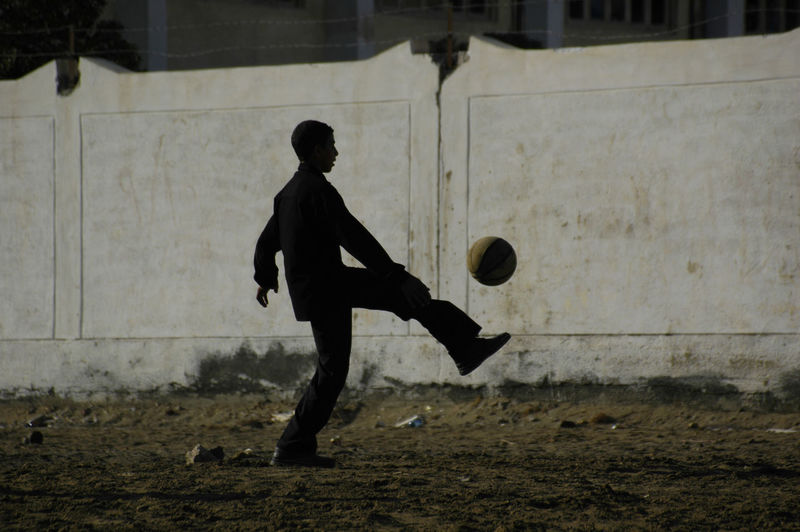 Boy playing soccer on field against wall