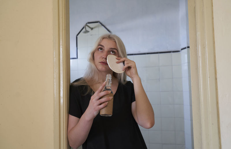 Full length of a young woman drinking glass door