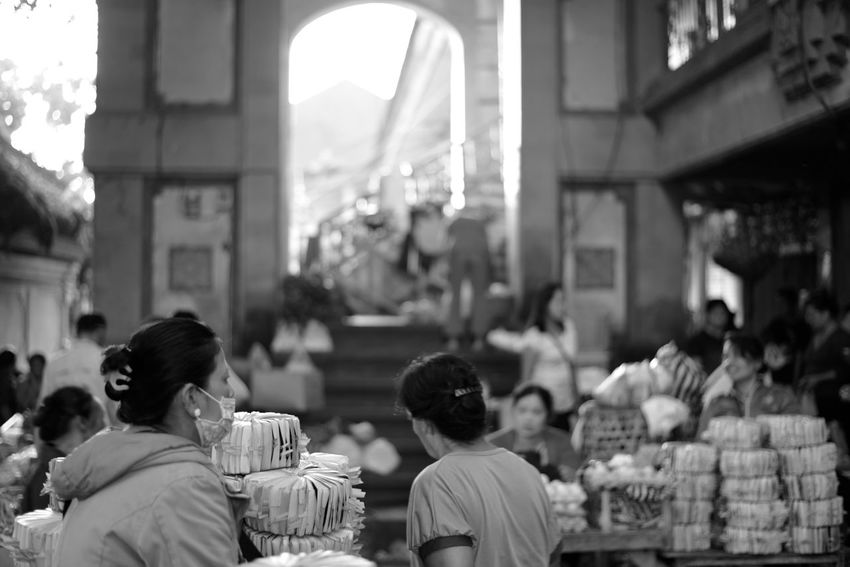 early morning light at the pasar (market) a young women sells pre-made canang (traditional Balinese offerings). canang offerings are given several times a day in Bali. so pre-made offerings cater to the busy Balinese women who might have to juggle daily spirituality with a career and family. Adult Arch Architecture B&w Street Photography Bali Bali, Indonesia Black And White Bokeh City Life Crowd Everybodystreet Everydayasia Large Group Of People Market Stall Monochrome Morning Light Pasar People Real People Street Photography The City Light Ubud Urban Urban Lifestyle Women