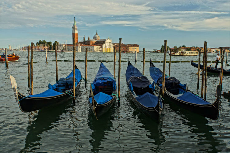 Gondolas moored in canal against cloudy sky