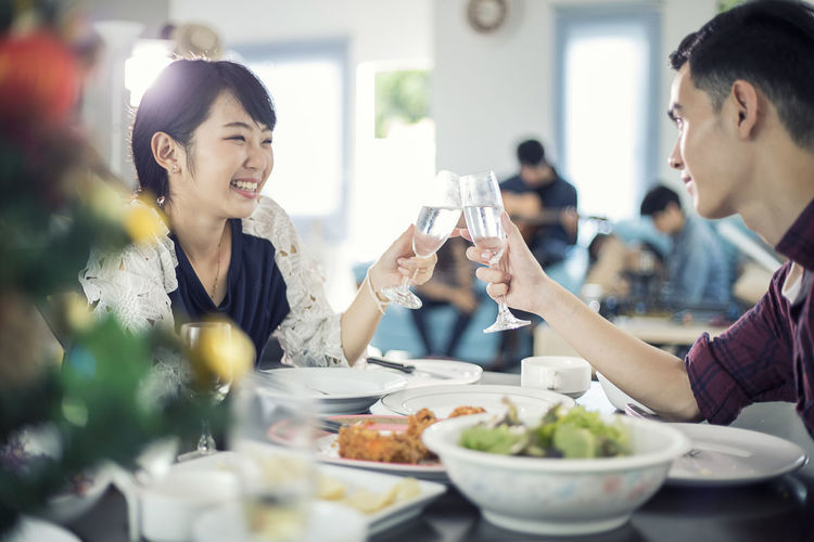 Friends Toasting Drinks While Having Meal In Restaurant