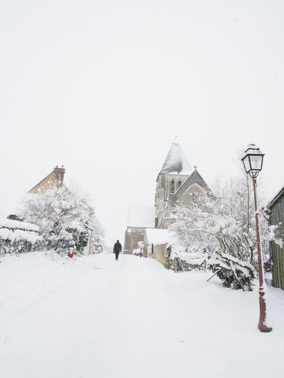 walking in snow in beautiful village France Architecture Beauty In Nature Building Exterior Built Structure Clear Sky Cold Temperature Day Full Length Nature Old Church One Person Outdoors Peacfull Place People Rare Picture Real People Sky Snow Travel Destinations Tree Warm Clothing Weather White Color Winter