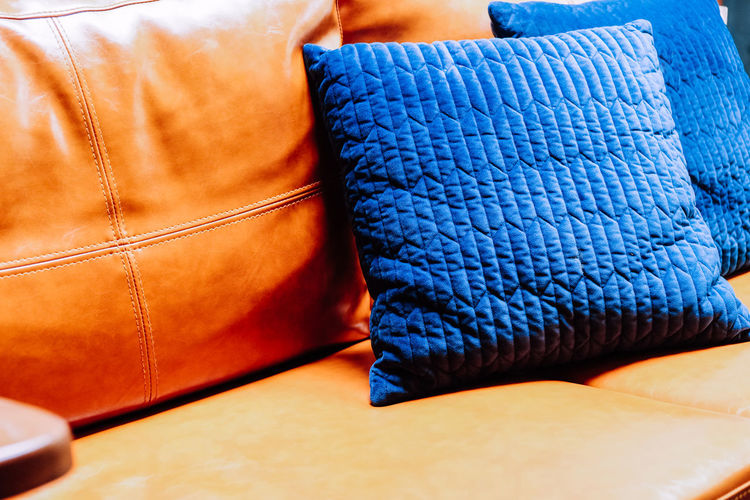 Close up detail of blue pillow on leather sofa Decor Leather Living Orange Pillow Bag Blue Body Part Brown Business Casual Clothing Close-up Clothing Cushion Decoration Decorations Decorative Denim Fashion Furniture Furniture Details Home Interior Indoors  Interior Design Jeans Leather Leather Sofa Living Room No People Orange Color Retail  Sofa Textile