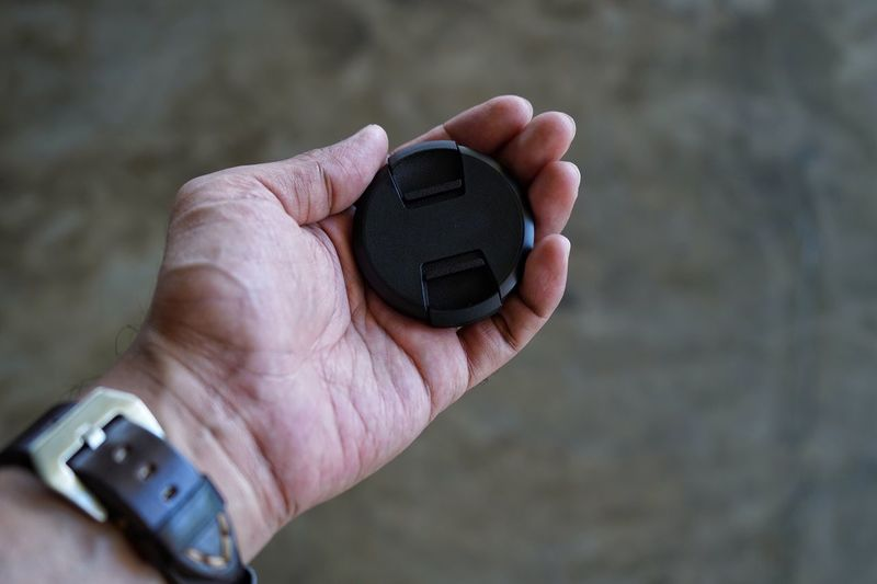Close-Up Of Hand Holding Lens Cover