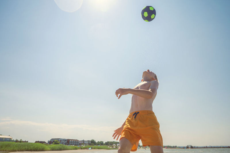 Full length of young woman playing with ball against sky
