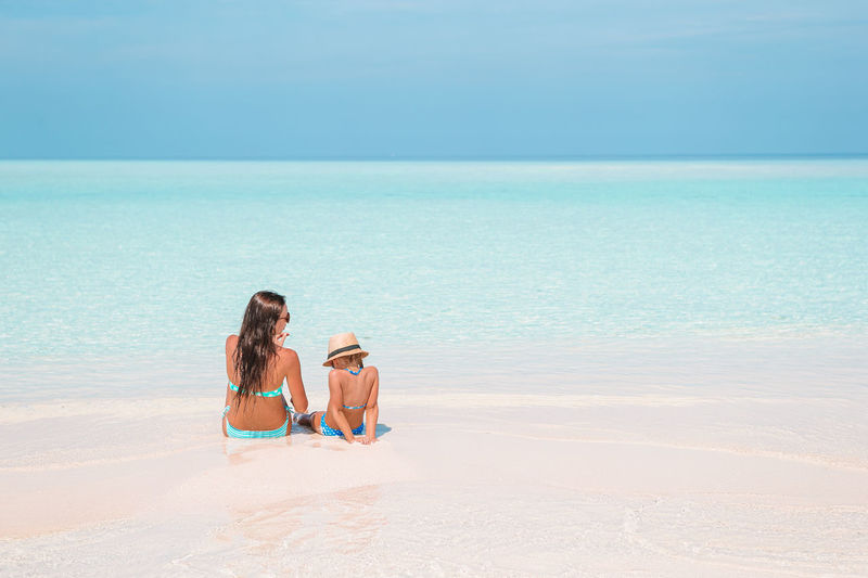 Friends sitting on beach against sky
