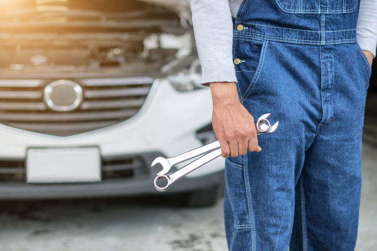 Midsection of man holding wrenches while standing by car