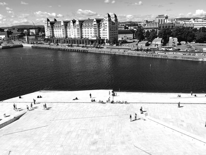 People Walking At Oslo Opera House Against City Skyline
