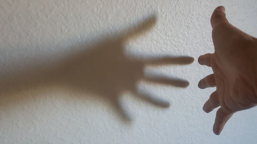 Close-up of person hand on wall