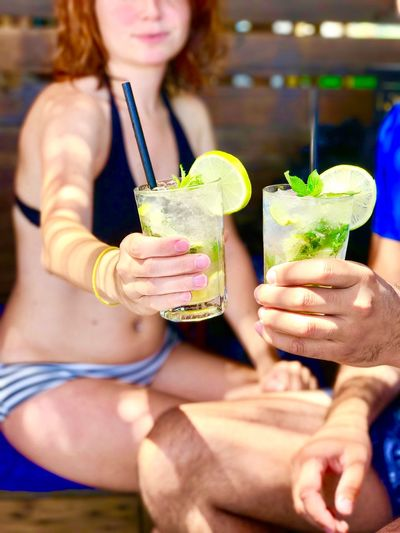 Close-Up Of Couple Holding Mojito Glasses During Summer Vacations