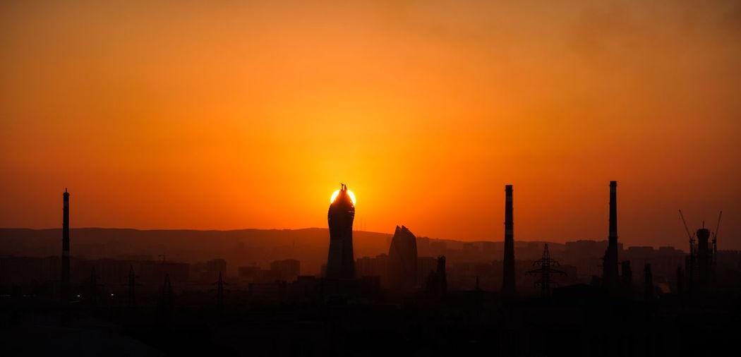 Silhouette temple against orange sky during sunrise