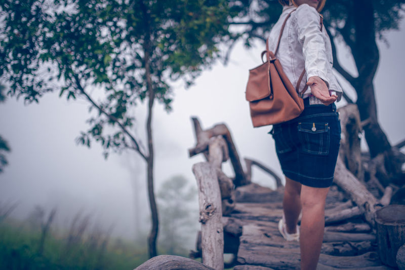 Low section of mid adult woman with backpack walking on boardwalk