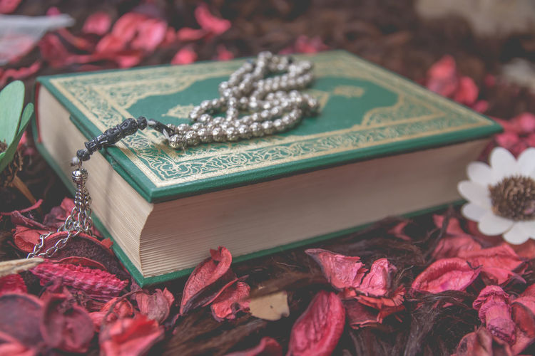 Close-up of koran with prayer beads and flowers on table