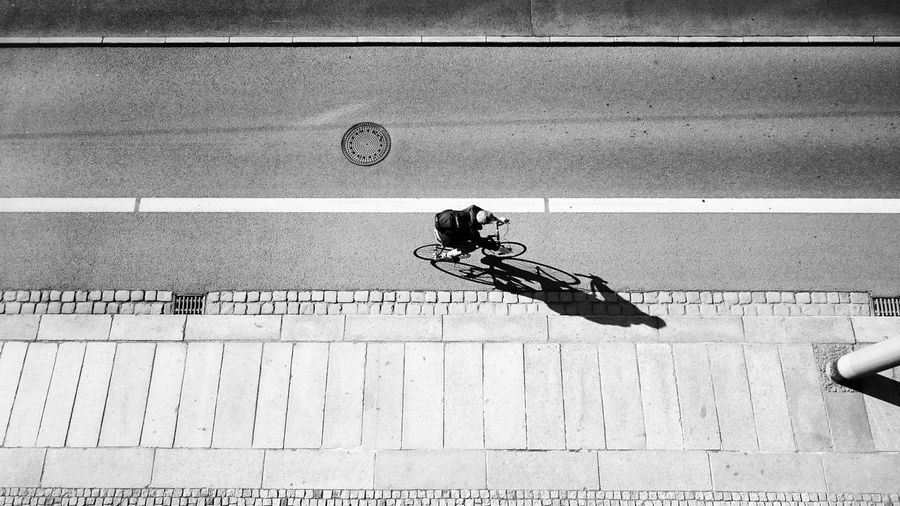 Hotel window with a view A Bird's Eye View View From Above Airial View Arial Shot Looking Down Bicycle Riding Bike Blackandwhite Black And White Streetphotography Concrete Jungle Street Outside Watching People Lines Pavement Textures And Surfaces WINDOW WITH A VIEW Day Selective Focus Shadow Shadows & Lights Shadowplay Creative Light And Shadow