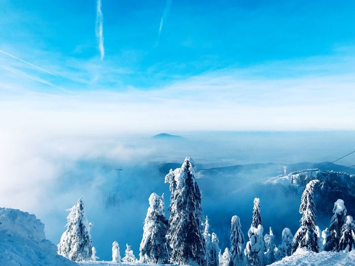 Panoramic view of snowcapped mountains against blue sky