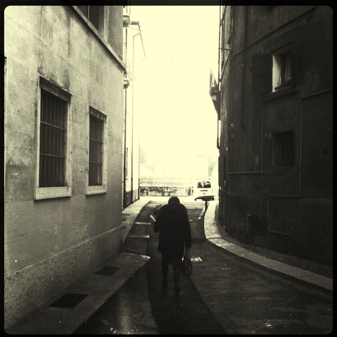 Silhouette Man Walking On Pathway Along Buildings