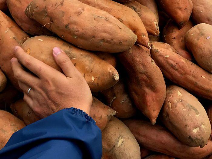 Close-up of hand touching sweet potatoes