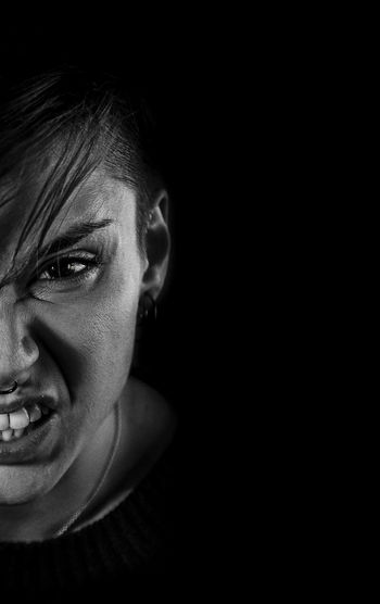 Close-up portrait of angry young woman against black background
