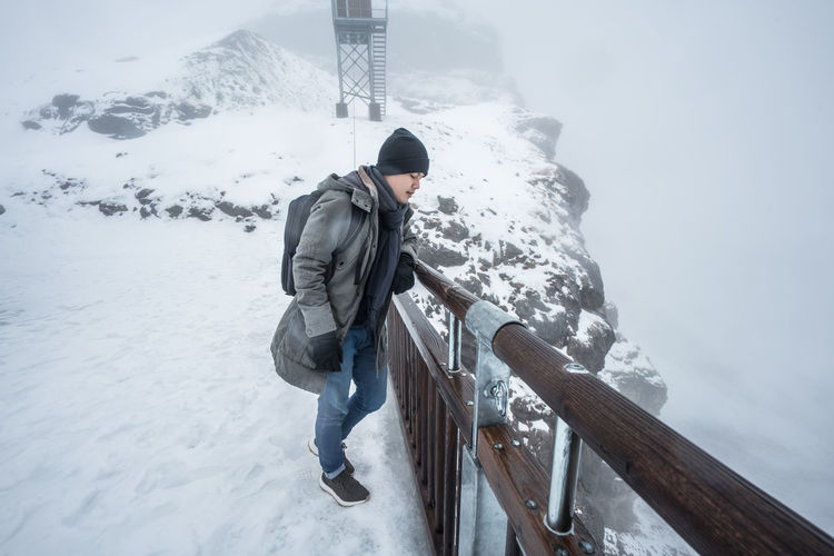 Warm Clothing One Person Young Adult Full Length Nature Outdoors Standing Day Lifestyles Mountain Cold Temperature Weather Leisure Activity Frozen Young Men Adventure Real People Young Women Winter Snow Beauty In Nature Snowing Climbing Sky Shades Of Winter