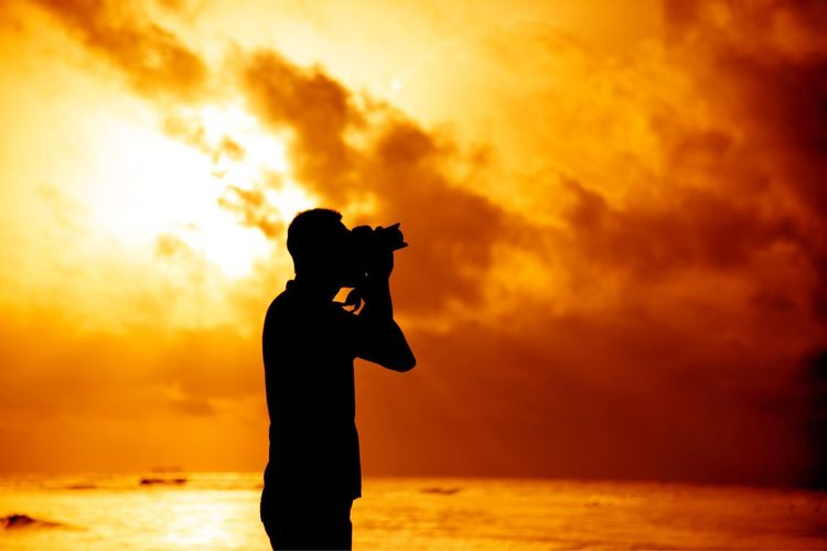 Silhouette Man Photographing At Beach Against Orange Sky