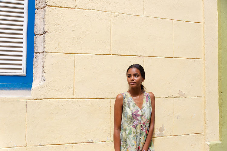 Beautiful young woman looking away while standing against wall