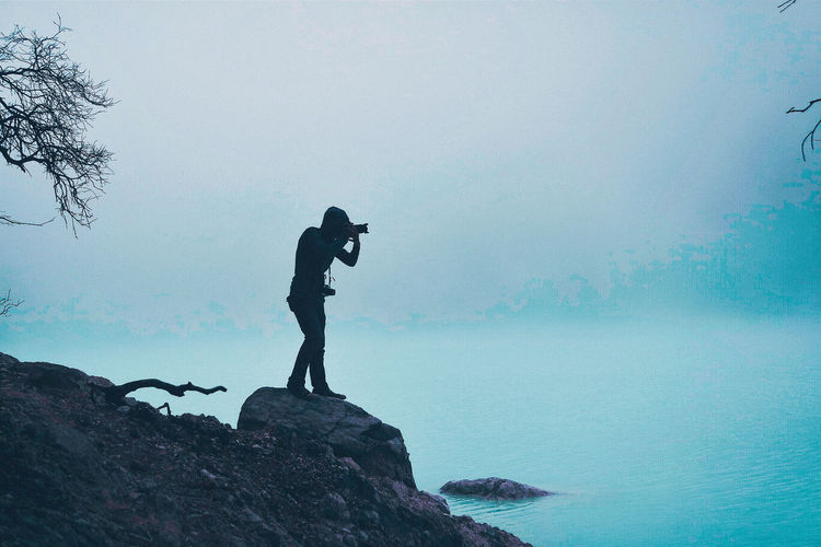 Capturing photos at kawah putih Real People Rock Water Lifestyles Leisure Activity One Person Rock - Object Solid Beauty In Nature Nature Tranquil Scene Standing Full Length Outdoors Activity Foggy Fog Cold Temperature Photographer Camera