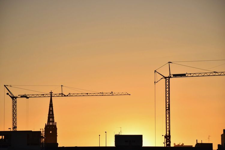 Low angle view of silhouette cranes against orange sky