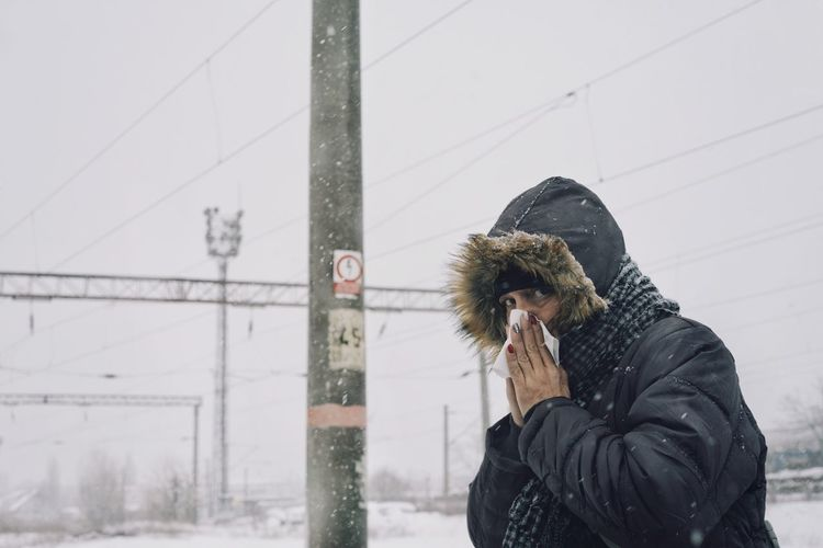 Portrait Of Woman Sneezing Against Sky During Winter