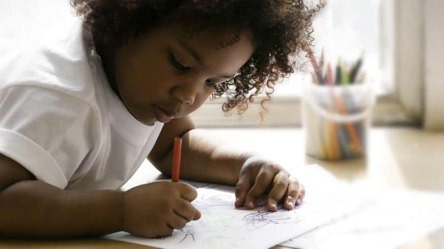 Little african girl painting and drawing on paper. preschool girl lying writing on floor.