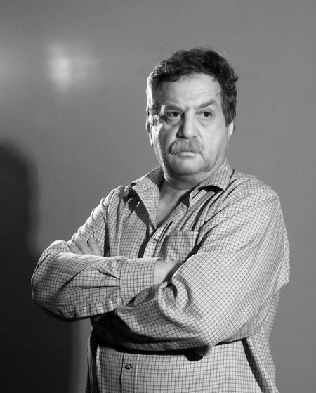 Mature man with arms crossed standing by wall
