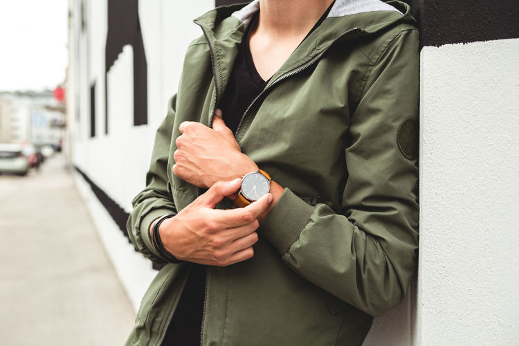Young Man casually dressed wearing analog watch in the Urban environment Midsection One Person Real People Men Hand Human Hand Standing Holding Human Body Part Focus On Foreground Architecture Day Lifestyles Clothing Communication Front View Outdoors Adult City Waiting Finger Watch Wrist Watch Jewellery Jewelry Young Adult Young Men City City Life Urban Street