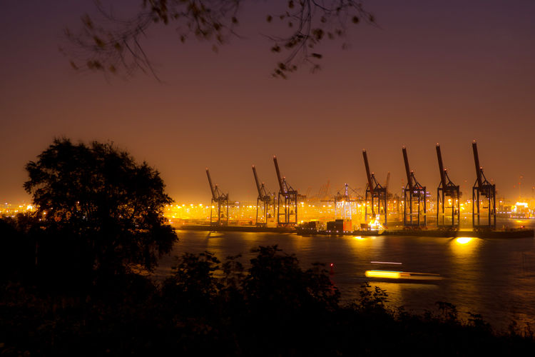 Silhouette cranes at harbor against sky during sunset