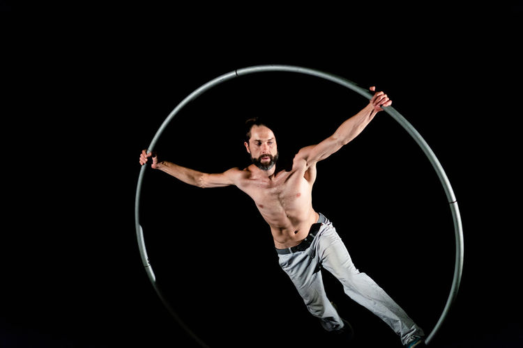 Circus Adult Agility Arms Raised Balance Black Background Effort Flexibility Front View Human Arm Indoors  Men Motion One Person Performance Plastic Hoop Shirtless Skill  Sport Strength Studio Shot Vitality Young Adult