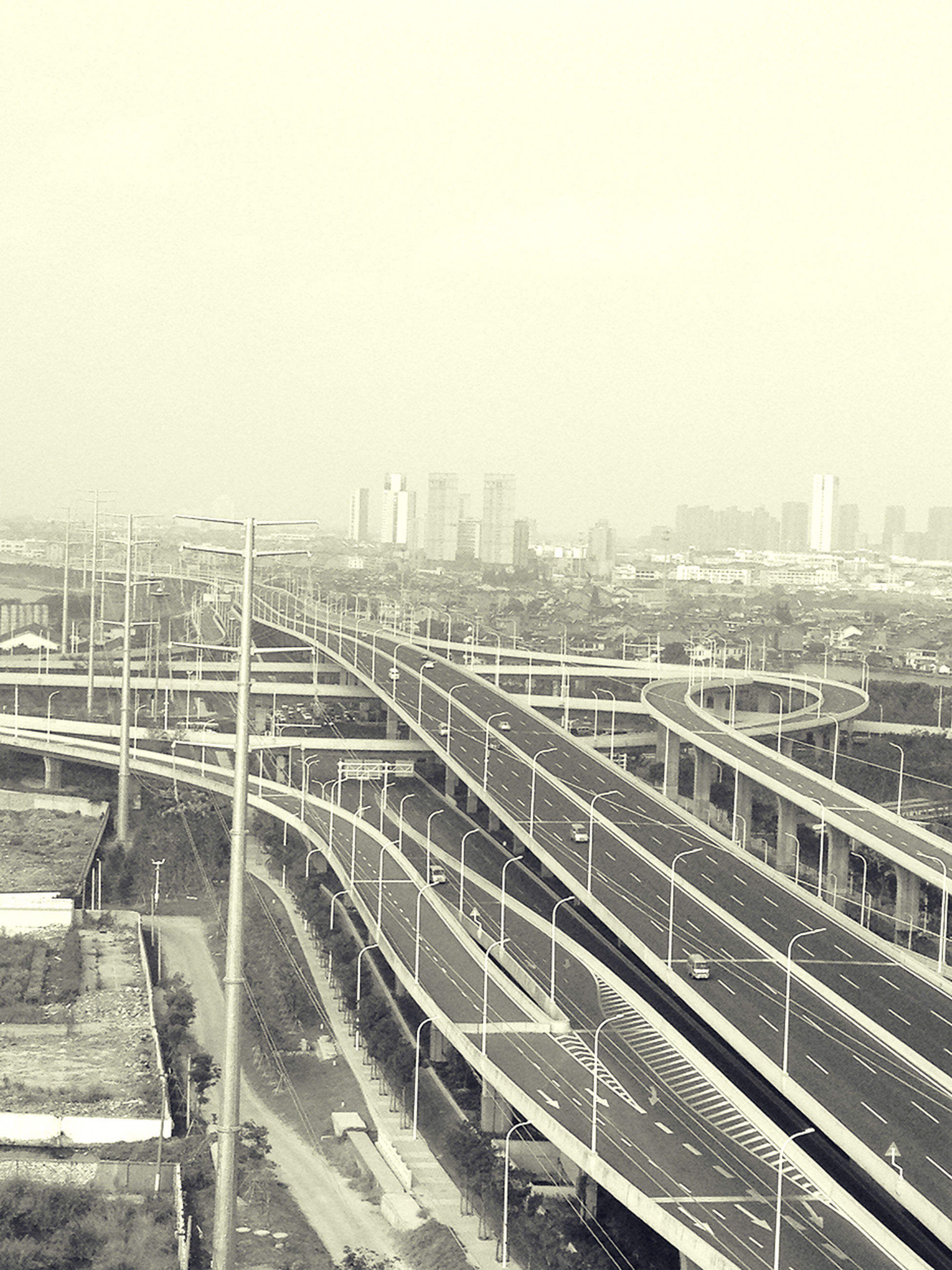 built structure, architecture, clear sky, building exterior, copy space, city, cityscape, high angle view, metal, day, outdoors, no people, development, sky, railing, bridge - man made structure, foggy, construction site, industry