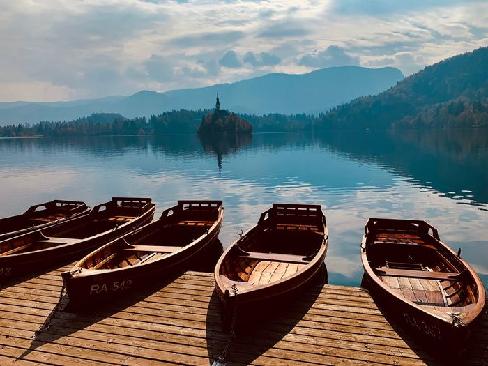 Bled Slovenia Nature Beauty In Nature Scenics - Nature Nautical Vessel Lake Day Transportation No People Beach Outdoors Water Transportation Mode Of Transportation Tranquility Nature Beauty In Nature Sky Moored Cloud - Sky Mountain Wood - Material Travel Tranquil Scene Reflection Rowboat