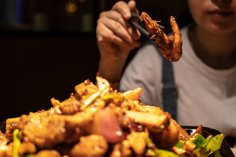 Midsection Of Woman Holding Fried Shrimp In Chopsticks At Restaurant
