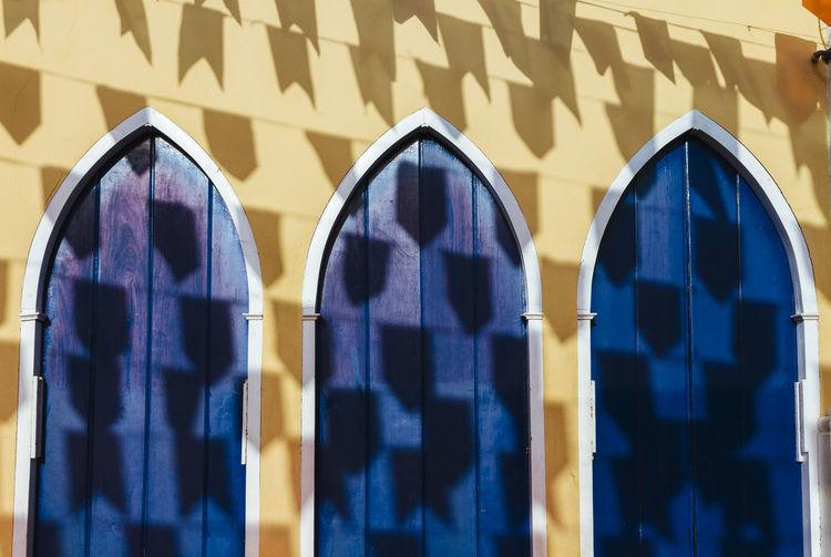 Shadow Of Flags On Blue Doors