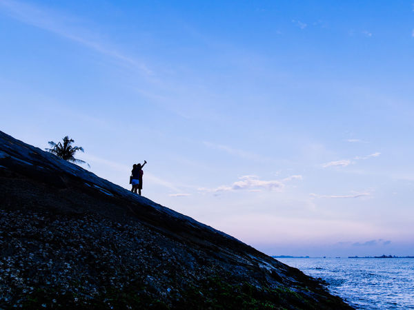 Silhouette of couple taking selfies on rocky groyne under blue sky Sky Real People Leisure Activity Lifestyles Beauty In Nature People Rock Outdoors Horizon Over Water Selfie Photographing Couple Couple - Relationship Togetherness Palm Tree Palm Groyne Groin Sea Water Blue Sky Evening Morning Evening Sky Morning Sky