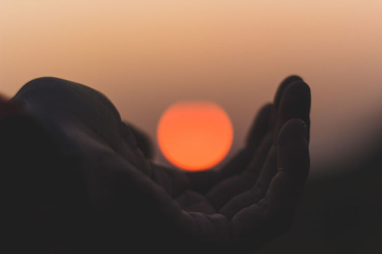 Optical Illusion Of Hand Holding Sun At Sunset
