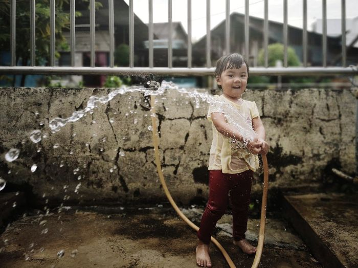 Full length portrait of girl playing with garden hose