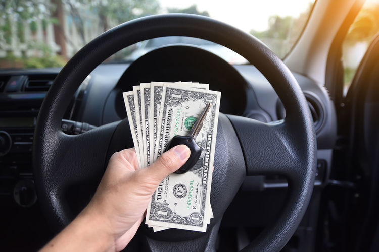 Cropped hand holding key with paper currency in car