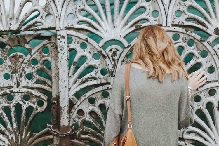 Rear View Of Woman Standing Against Rusty Gate